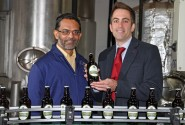 Des DSouza left of Wolf Brewery and Paul LeGrice of Abel Homes celebrate the first bottles of The Hops beer coming off the production line